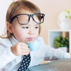 A joke image of a kid in a shirt and tie drinking coffee